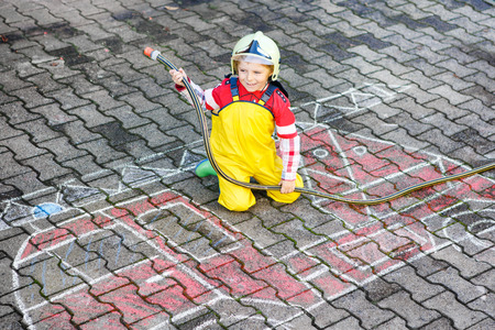 firefighter: Creative leisure for kids: Funny little boy having fun with fire truck picture drawing with chalk, outdoors Stock Photo