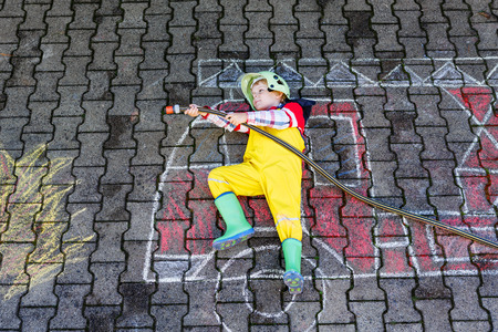 kids having fun: Creative leisure for kids: Little kid boy of four years having fun with fire truck picture drawing with chalk, outdoors. Dreaming of future profession. Stock Photo
