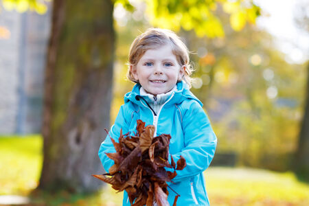 Little kid boy with yellow autumn leaves in park. Having fun on sunny warm october day photo
