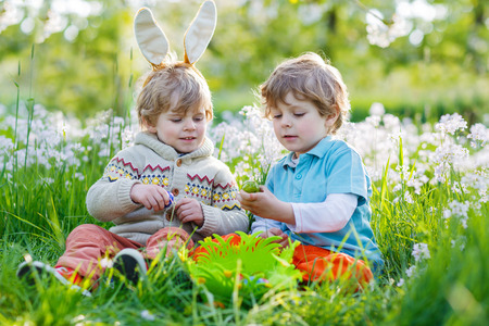 Two little boy friends in Easter bunny ears during traditional egg hunt in spring garden, outdoors. On warm sunny day with blooming trees on background. photo