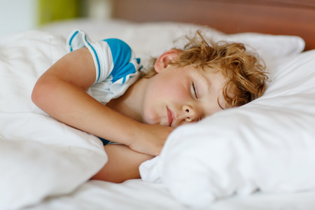Little blond boy sleeping in his bed Standard-Bild