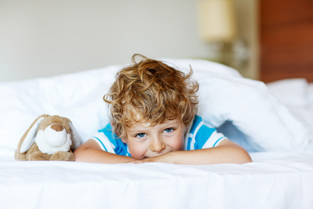 Adorable kid boy after sleeping in his white bed with toy.