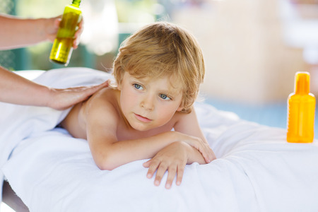 Beautiful little kid boy relaxing in spa with having thai massage.