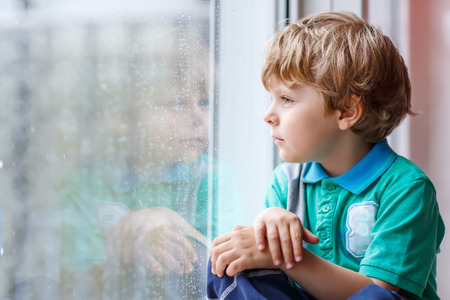 Adorable little blond kid boy sitting near window and looking on raindrops, indoors. Standard-Bild