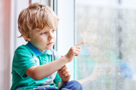Cute little blond kid boy sitting near window and looking on raindrops, indoors.