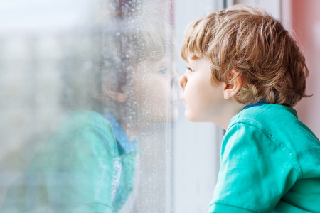 Lovely little blond child sitting near window and looking on raindrops, indoors. photo