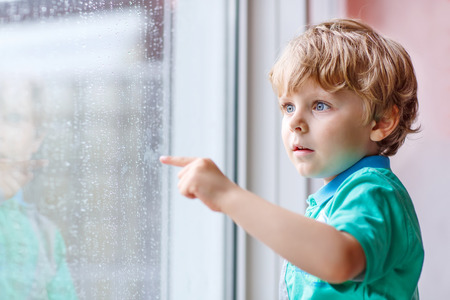 Adorable little blond kid boy sitting near window and looking on raindrops, indoors. photo