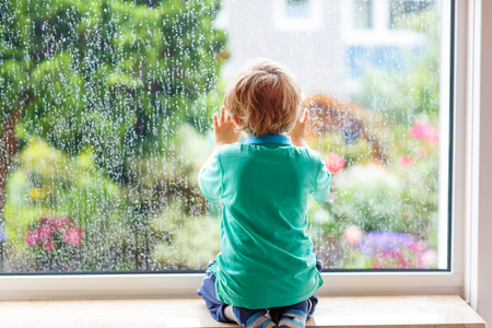 Adorable little blond child sitting near window and looking on raindrops, indoors. Foto de archivo