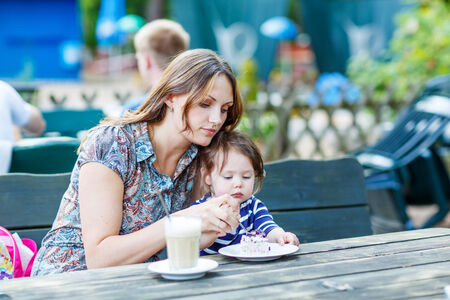 Beautiful young mother relaxing together with her little daughter, adorable toddler girl, in summer outdoors cafe drinking coffee. photo