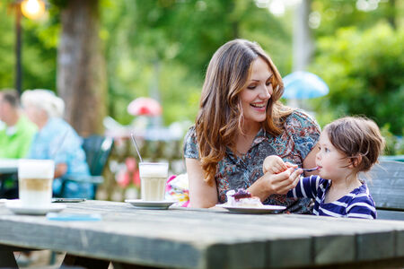 adult child: Young mother relaxing together with her little child, adorable toddler girl, in summer outdoors cafe drinking coffee and eating muffin or cupcke. Stock Photo