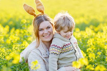 Little toddler boy and his mother in Easter bunny ears having fun, celebrating traditional Easter holiday. In yellow rape field, outdoors, on warm spring day. photo
