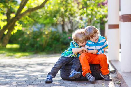 2 to 3 years: Due ragazzini fratello capretto abbracciare e divertirsi all'aria aperta, nel giardino di casa calda giornata estiva. Fratello concetto di amore.
