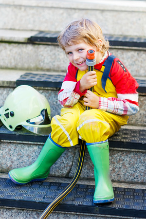 kids having fun: Creative leisure for kids: Funny little child of four years having fun as fireman, in uniform and helmet.