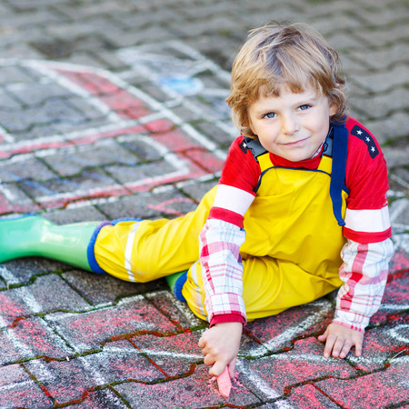 3 4 years: Creative leisure for kids: adorable child clothing as fireman having fun with fire truck picture drawing with chalk, outdoors. Dreaming of future profession.