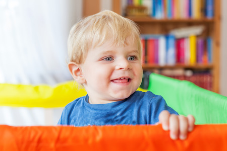 Cute little baby boy playing in colorful playpen, indoors. Beautiful child having fun at home. photo