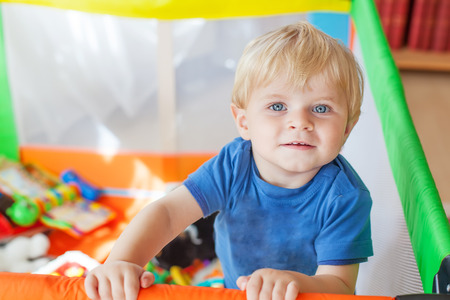 playpen: Cute little baby boy playing in colorful playpen, indoors. Beautiful child having fun at nursery. Stock Photo
