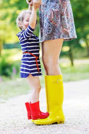 Young mother and little adorable child girl in rubber boots having fun together, family look, in summer park on sunny warm day. Long legs of woman.