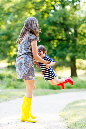 Little kid girl and her mom in rubber boots having fun together, family look, in summer park on sunny warm day. Long legs of woman. photo