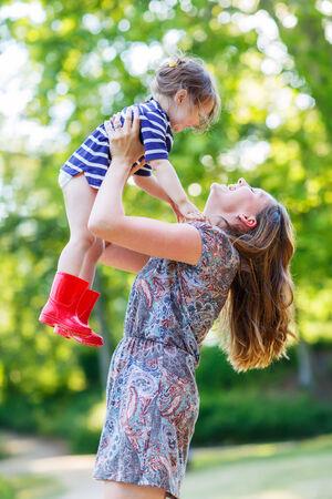 botas de lluvia: Hermosa joven madre sosteniendo a su ni�a feliz ni�o en brazos en las botas de lluvia de color rojo en el parque de verano en d�a c�lido y soleado. Familia feliz: madre y el concepto hija.