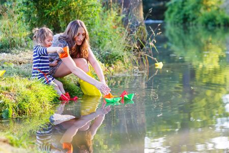Young beautiful woman and her little daughter playing together with paper boats in a river. Creative leisure with kids. photo