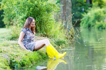 Young beautiful woman sitting in yellow rain rubber boats by a river in summer. photo
