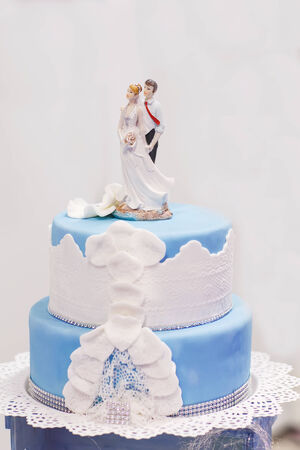 Wedding cake in soft blue and white, with bride and groom figure on the top.