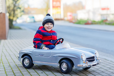 Happy little boy driving big vintage old toy car and having fun, outdoors. Kids leisure on cold day in winter, autumn or spring. Stock Photo
