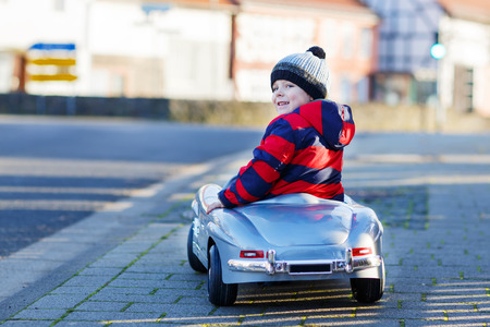 Funny cute child in red jacket driving big vintage old toy car and having fun, outdoors. Kids leisure on cold day in winter, autumn or spring.