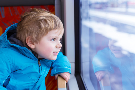 Little kid boy looking out train window outside, while it moving. Going on vacations and traveling by railway in winter. photo