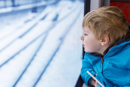Adorable little kid looking out train window outside, while it moving. Going on vacations and traveling by railway in winter. photo