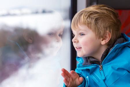 Mooie peuter jongen kijkt uit trein venster naar buiten, terwijl het bewegen. Gaat u op vakantie en reizen per spoor in de winter.