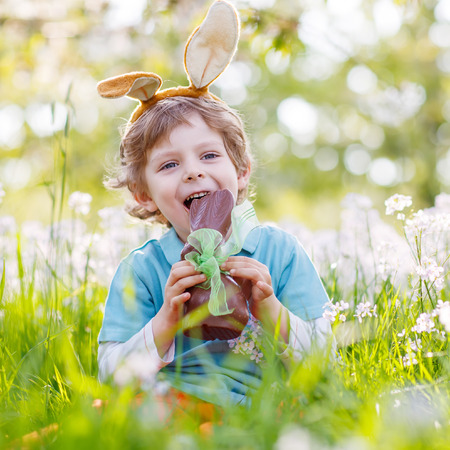 Happy little toddler boy eating chocolate and wearing Easter bunny ears, sitting in blooming garden on warm sunny day. Celebrating Easter traditional holiday.