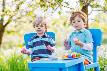 Family of two siblings: Cute twin boys wearing Easter bunny ears, painting colorful eggs and having fun outdoors. Traditional egg hunt. photo
