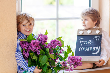 one child: Two happy adorable little sibling boys with blooming lilac flowers and blackboard as gift for their mum on mothers day, indoor. Selective focus on one child.