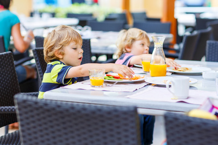 Two little kid boys having healthy breakfast in hotel restaurant or city cafe. Selective focus. Archivio Fotografico