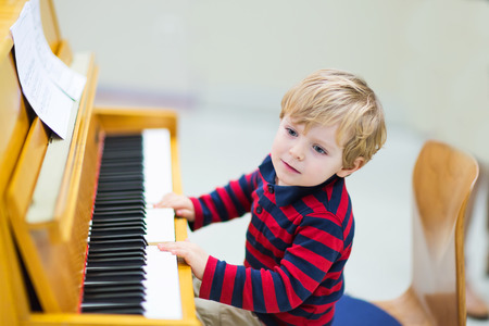music education: Two years old happy toddler boy playing piano. Early music education for little kids. child at school, learning music instrument. Stock Photo