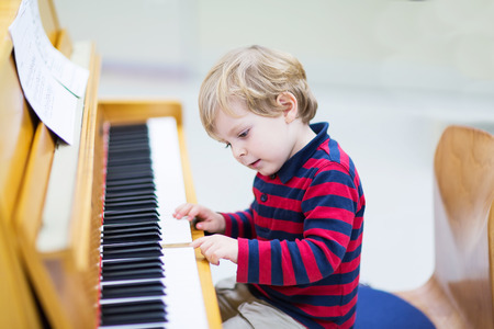 Two years old funny positive toddler child playing piano. Early music education for little kids. child at school, learning music instrument.