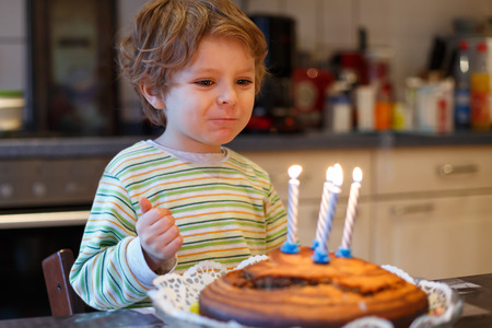 and four of the year: Adorable four year old boy celebrating his birthday and blowing off the candles on the cake, indoor Stock Photo