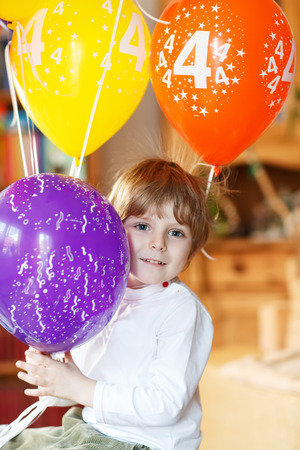 kidsroom: Happy little boy celebrating his 4 birthday with colorful balloons, indoor in kidsroom. Stock Photo