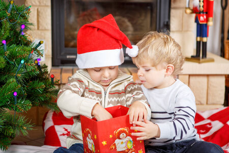 fireplace family: Two little sibling boys being happy about christmas presents, indoor with traditional decoration and fireplace. Family celebrating holiday.