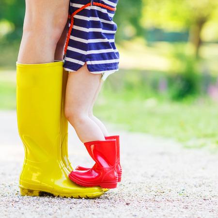 Benen van de jonge vrouw en haar kleine meisje dochter in regenlaarzen. Stockfoto