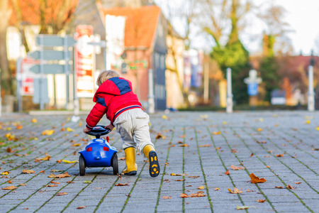 Funny cute child in red jacket driving blue toy car and having fun, outdoors. Kids leisure on cold day in winter, autumn or spring.