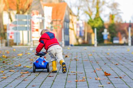 juguetes antiguos: Ni�o lindo divertido en la chaqueta roja que conduce el coche de juguete azul y divertirse, al aire libre. Ni�os ocio en d�a fr�o en invierno, oto�o o primavera.