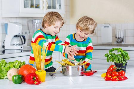 whithe: Dos ni�os gemelos divertidos cocinar comida italiana con spahetti y verduras frescas en la cocina whithe del hogar. Hijos de hermanos con camisas de colores.