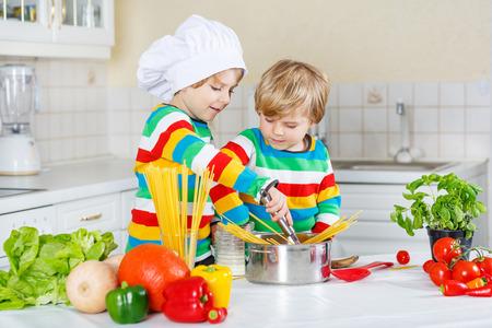 whithe: Dos peque�os amigos cocinar comida italiana con spahetti y verduras frescas en la cocina whithe del hogar. Hijos de hermanos con camisas de colores.