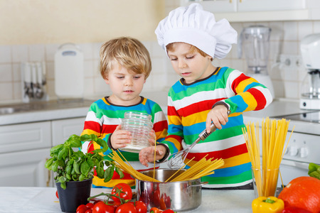 whithe: Two cute little brothers cooking italian meal with spahetti and fresh vegetables in homes whithe kitchen. Sibling children in colorful shirts. Stock Photo