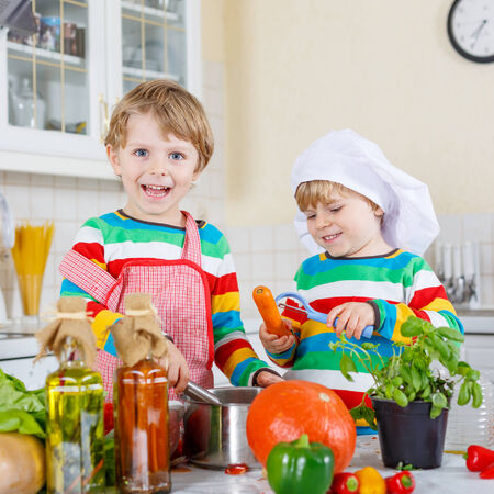 funny tomatoes: Two cute little children cooking italian soup and meal with fresh vegetables in homes white kitchen. Sibling boys in colorful shirts.