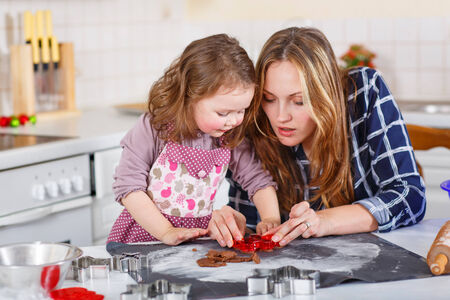 new mothers: Happy mother, young woman in red santa hat baking christmas cookies together with her little daughter, cute blonde kid girl, sitting at the table in domestic kitchen Stock Photo