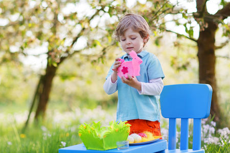 Beautiful little preschoool boy playinig with colorful eggs and having fun outdoors. photo