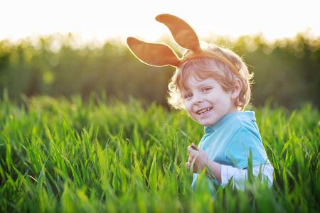 oreja: Muchacho divertido de 3 a�os con orejas de conejo de Pascua jugando en la hierba verde en d�a soleado de primavera, celebrando la fiesta de Pascua Foto de archivo